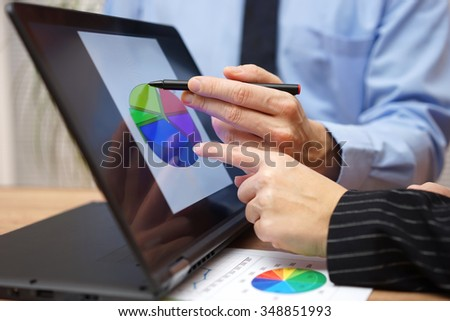business team is working  during meeting on report with financial diagram on laptop screen, pointing with finger at graph - stock photo