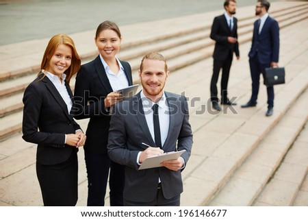 Business team looking at camera on background of two men interacting outside - stock photo
