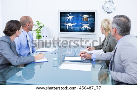 Business team looking at time clock against composite image of four drones - stock photo