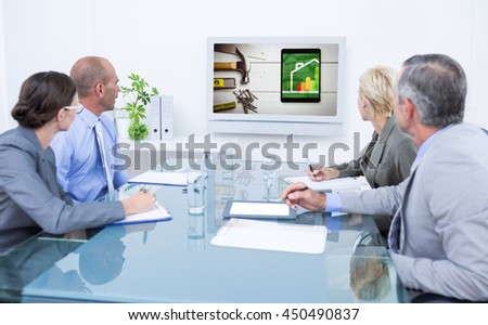Business team looking at time clock against energy efficient house graphic against a background - stock photo