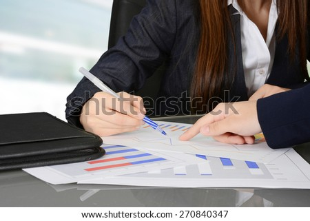 Business team looking over and analyzing data charts - stock photo