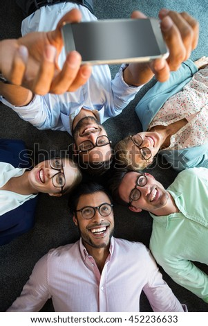 Business team lying on the floor with head together and taking selfie in the office - stock photo