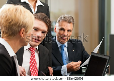 Business - team meeting in an office with laptop, the female boss with her employees - stock photo