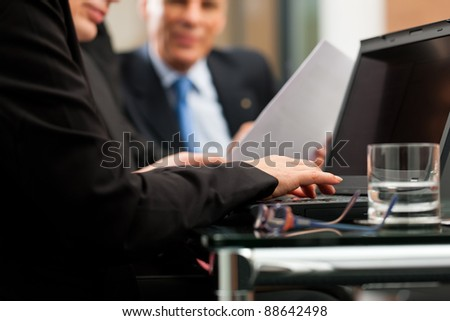 Business - team meeting in an office with laptop, the woman in front is typing - stock photo