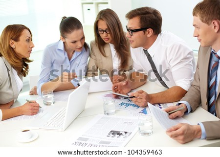Business team of five holding a briefing to discuss the latest ideas concerning the project - stock photo