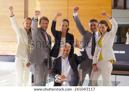 Business team of six smiling executives rising fist in the air. - stock photo