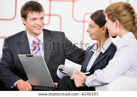 Business team of three people discussing a new project in room - stock photo
