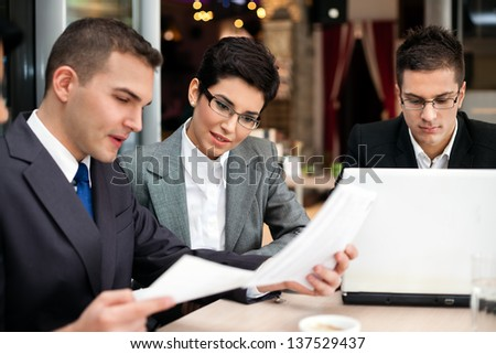 business team of three sitting in cafe and planning work - stock photo