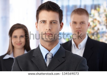 Business team portrait, focus on smart and handsome businessman, coworkers in background. - stock photo