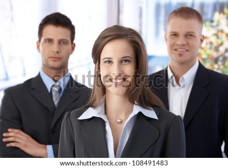 Business team portrait, happy confident businesswoman in focus, businessmen in background. - stock photo