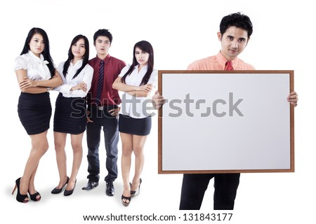 Business team presenting a blank whiteboard on white background - stock photo