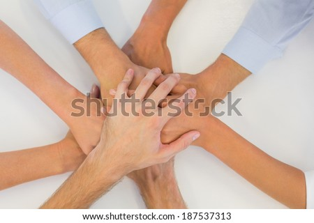 Business team putting their hands together in the office - stock photo