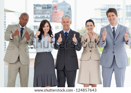 Business team putting their thumbs up to show a success - stock photo