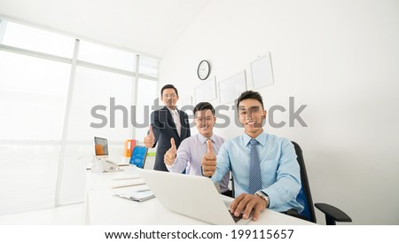 Business team showing thumbs up as a symbol of success - stock photo