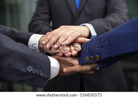 Business team showing union with their hands together forming a pile - stock photo