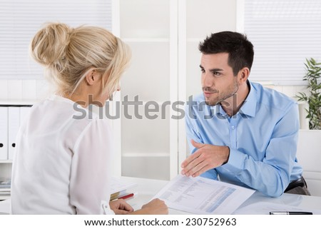 Business team sitting at desk in a meeting talking about financial report. - stock photo