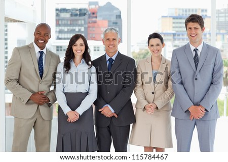 Business team smiling and standing upright side by side with their hands crossed - stock photo