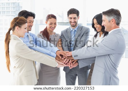 Business team stacking their hands together while smiling - stock photo