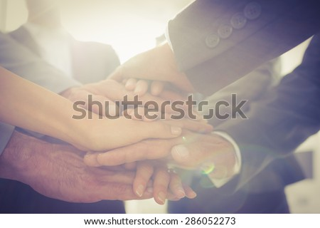 Business team standing hands together in the office - stock photo