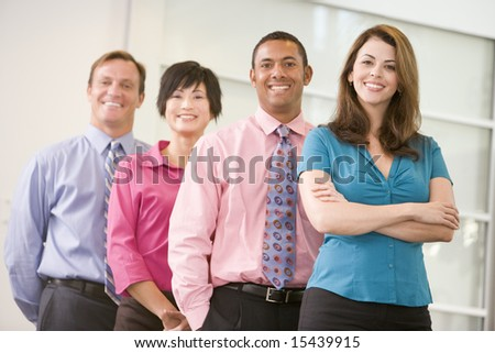 Business team standing indoors smiling - stock photo