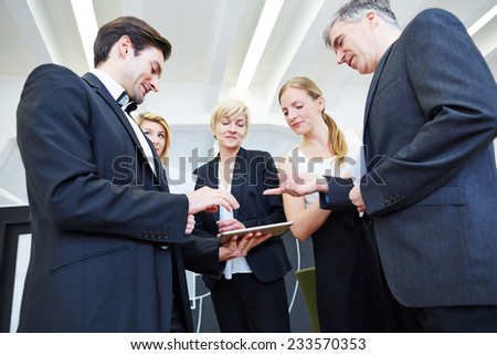 Business team standing with tablet PC in office and discussing - stock photo