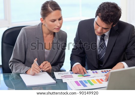 Business team studying statistics in a meeting room - stock photo