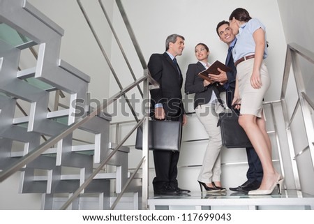Business team talking to each other in office stairway - stock photo
