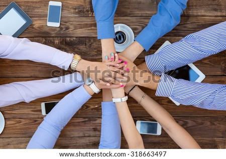 Business Team Unity Group of People at Vintage Wood Table Holding Hands Round Top View High-Tech Electronic Gadgets on Desk Tablet Computer Coffee Telephone - stock photo