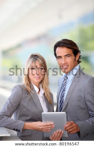 Business team using electronic tablet outside offices building - stock photo
