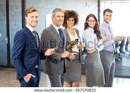Business team using their mobile phone in the office - stock photo