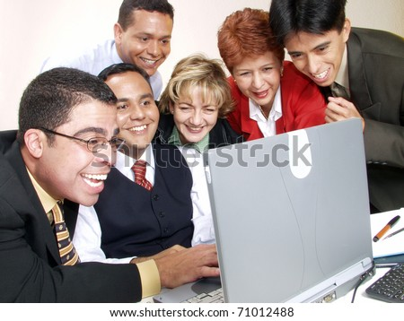 Business team watching a computer in an office. - stock photo