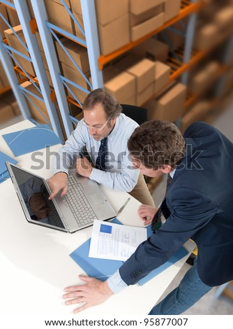 Business team with a storage warehouse at the background - stock photo