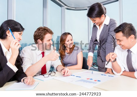 business team with Asian and Caucasian members discussing earnings with financial graphs on the table - stock photo