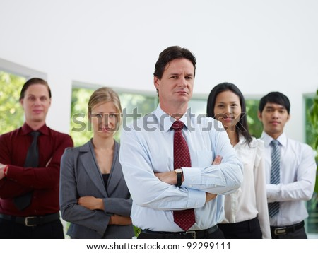 Business team with men and women looking at camera with confidence and pride in office. Copy space, front view - stock photo