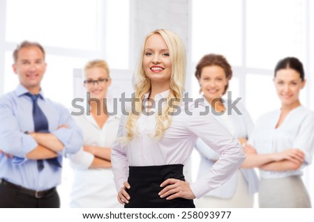 business, team work and people concept - smiling businesswoman, student or secretary over group of colleagues over office background - stock photo