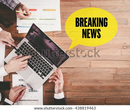 BUSINESS TEAM WORKING IN OFFICE WITH BREAKING NEWS SPEECH BUBBLE ON DESK - stock photo