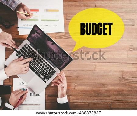 BUSINESS TEAM WORKING IN OFFICE WITH BUDGET SPEECH BUBBLE ON DESK - stock photo