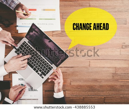 BUSINESS TEAM WORKING IN OFFICE WITH CHANGE AHEAD SPEECH BUBBLE ON DESK - stock photo