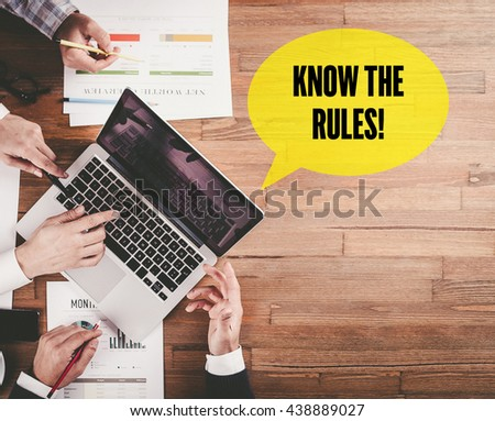 BUSINESS TEAM WORKING IN OFFICE WITH KNOW THE RULES! SPEECH BUBBLE ON DESK - stock photo