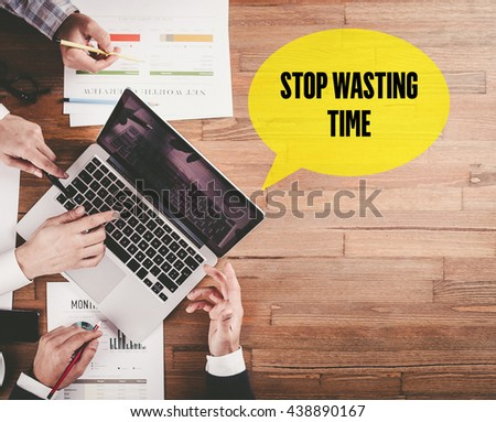BUSINESS TEAM WORKING IN OFFICE WITH STOP WASTING TIME SPEECH BUBBLE ON DESK - stock photo