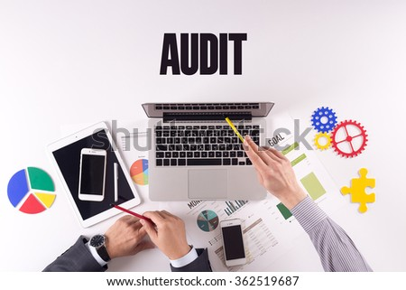 Business team working on desk with a single word AUDIT - stock photo