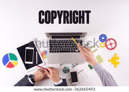 Business team working on desk with a single word COPYRIGHT - stock photo