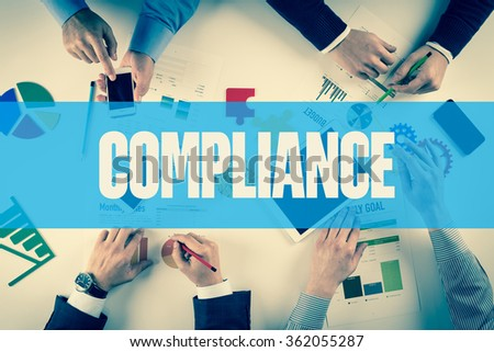 Business team working on desk with COMPLIANCE word - stock photo