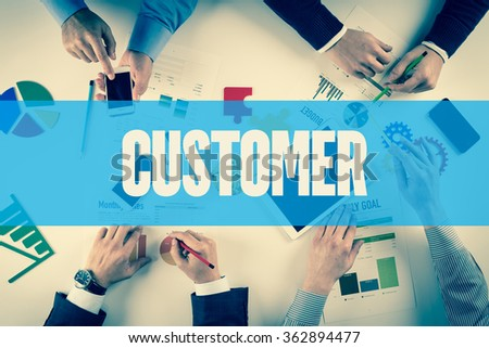 Business team working on desk with CUSTOMER word - stock photo