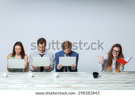 Business team working on their business project together at office on light gray background. all keeping computers. boss laughing. copyspace image.  - stock photo