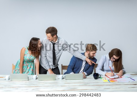 Business team working on their business project together at office on light gray background.  all smiling and looking at the boss. the boss is writing in a notebook. copyspace image.  - stock photo