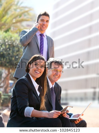Business team working outdoors with digital tablet and laptop. - stock photo