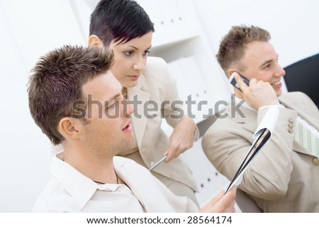 Business team working together in office. Man and woman reviewing notes in the foreground, happy man talking on mobile phone in the background. - stock photo