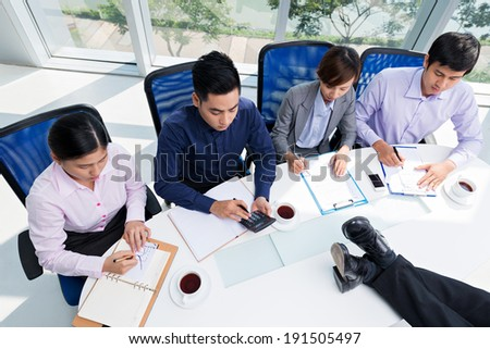 Business team working while their chief resting with his legs on the table - stock photo