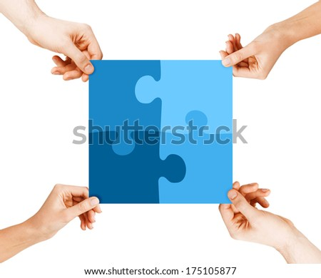 business, teamwork and collaboration concept - four hands connecting blue puzzle pieces - stock photo